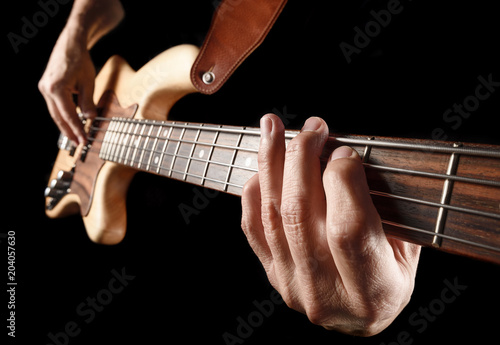 hands of rock bassist playing bass