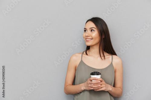 Portret urocza azjatykcia kobieta bierze oddaloną filiżankę