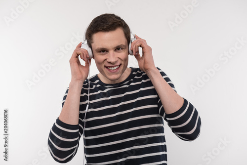 Music time. Joyful positive man smiling while putting on headphones