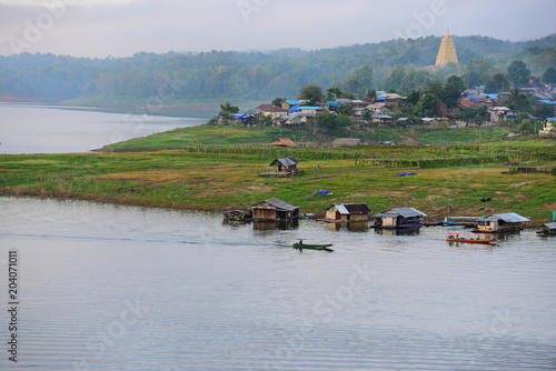 Fotobehang Donkergrijs View of the river and surrounding communities of the dam near the Mon Bridge at Khao Laem Dam, Sangklaburi, Thailand.