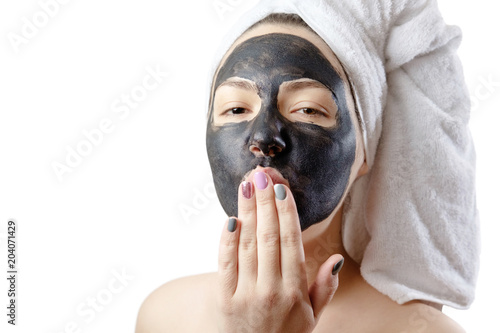 close-up portrait beautiful woman with facial black mask on white background, girl with a white towel on her head, satisfied and happy  smile, air kiss © denisval