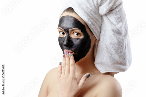 close-up portrait beautiful woman with facial black mask on white background, girl with a white towel on her head, satisfied and happy  smile, emotion of surprise © denisval