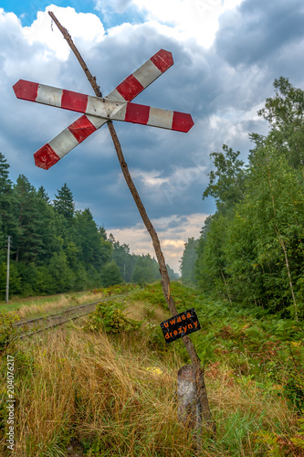 Uwaga - tablica ostrzegawcza w lesie przy torach kolejowych