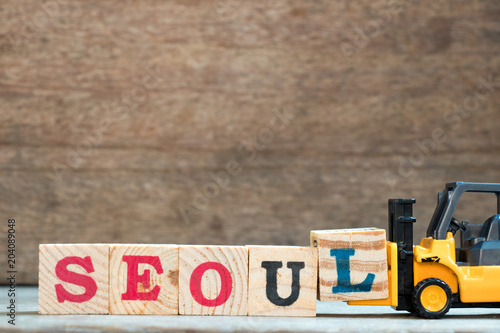 Plexiglas Seoel Yellow toy forklift hold letter block L to complete word seoul on wood background