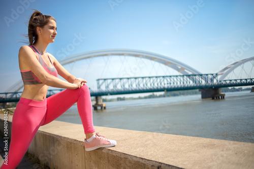 Aluminium School de yoga a young athletic-built girl stretches near bridge