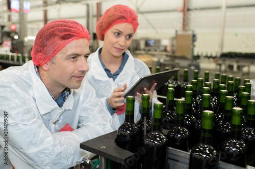 Fototapeta Workers looking proudly at wine bottles