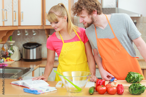 Wall mural Couple cooking in kitchen reading cookbook