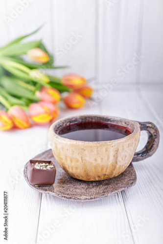 Hibiscus tea, luxury chocolates candy and flowers orange tulips on a white wooden background