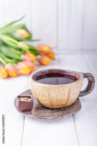 Hibiscus herbata, luksusowe czekoladki cukierki i kwiaty pomarańczowe tulipany na białym tle drewnianych