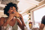Woman enjoying eating burger at restaurant - 204119487
