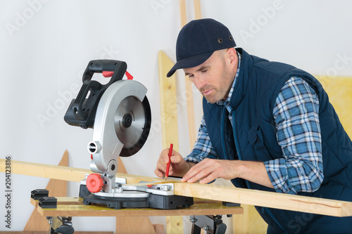 young carpenter is writing marks on a wood plank - 204123816