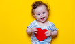 Little baby with heart shape toy on yellow background