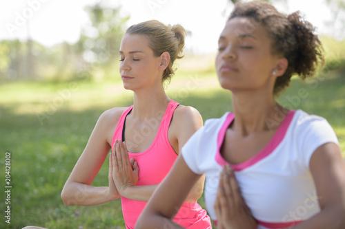 Aluminium School de yoga two girls doing yoga meditation
