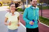 Young attractive couple running outside on sunny day - 204128268