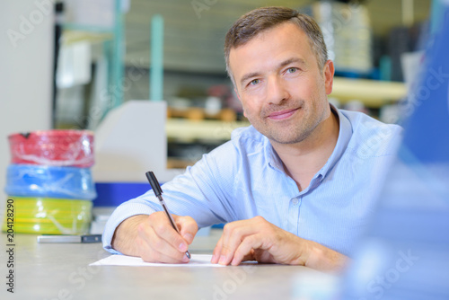 Man sat at table with pen and paper