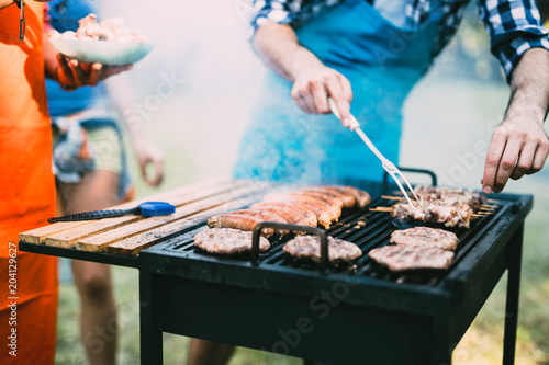 Young people grilling outdoors - 204129627