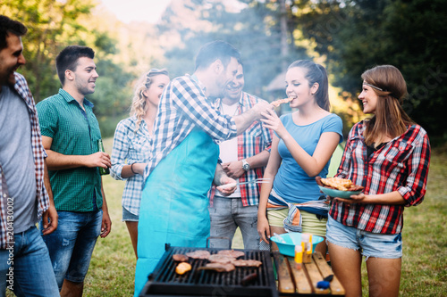 Happy students having barbecue on summer day - 204130002