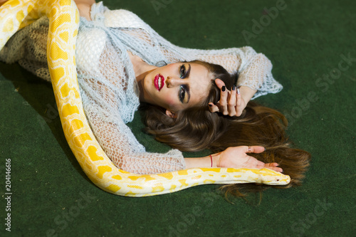 Beauty woman relax with albino python. Beauty model with makeup face and yellow snake. © tverdohlib