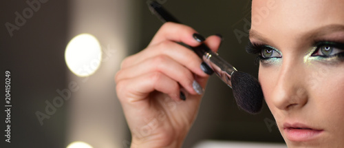 Woman applying dry cosmetic tonal foundation on face using makeup brush.