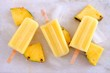 Quadro Group of pineapple ice pops. Top view over a white marble background.