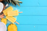 Pineapple coconut ice pops. Top view scene. Side border with copy space over a blue wood background.