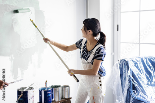 Asian woman panting house wall - 204161463
