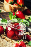 Strawberry jam, vintage wood background, selective focus