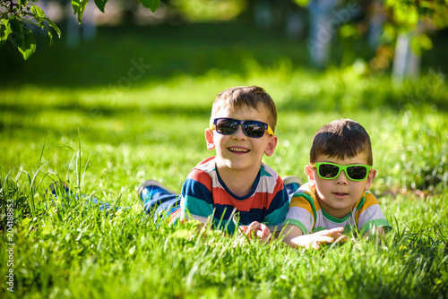 Fototapeta Happy smiling boy sibling brother relaxing on the grass. Close up view with copy space.