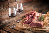 Two cups with red wine and raw beef steak on wooden table - 204191031