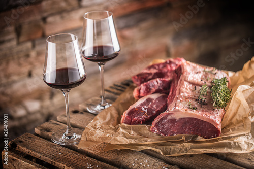 Plexiglas Steakhouse Two cups with red wine and raw beef steak on wooden table