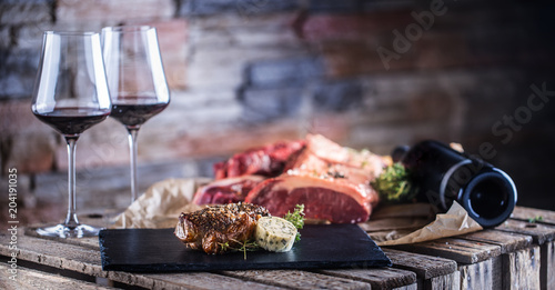Two cups with red wine roasted and raw beef steak on slate board - 204191035