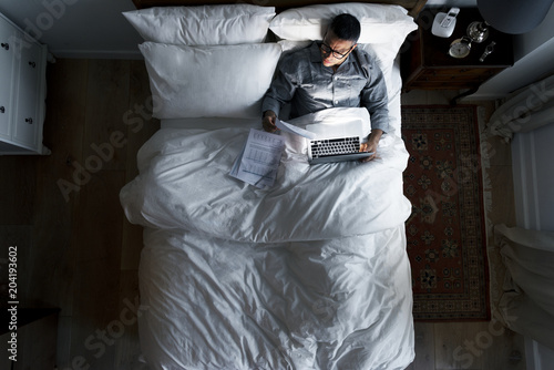 Business man on bed working at night - 204193602