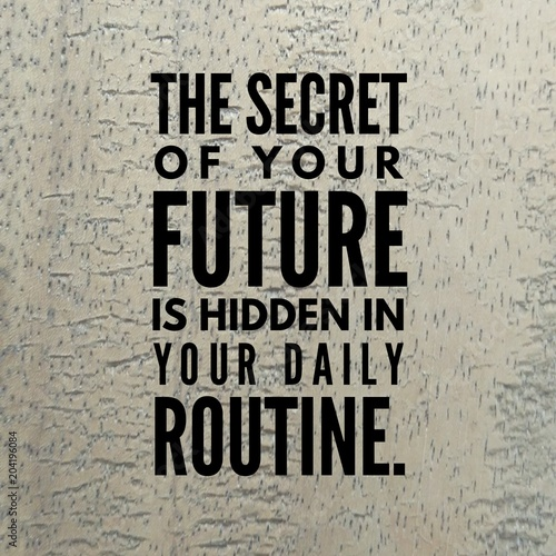 """Motivational quote """"The secret of your future is hidden in your daily routine."""" on a wooden background."""
