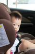 Portrait of cute Asian toddler boy sitting in car seat.