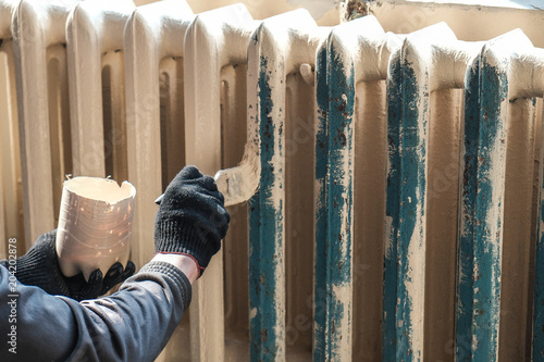 worker paints the metal water heating radiator