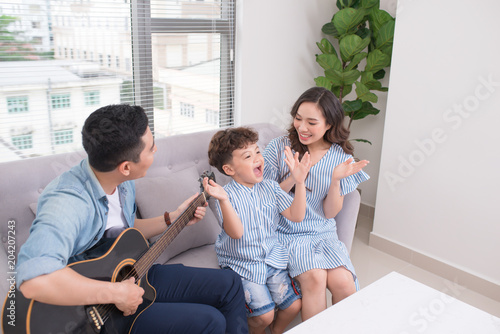Fotobehang Muziek Happy asian family teaching his son how to play the guitar