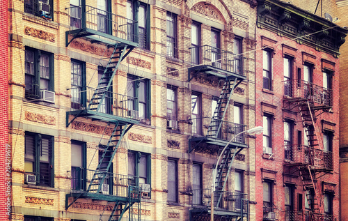 Vintage stylized picture of old buildings with fire escapes, one of New York City symbols, USA. - 204219619