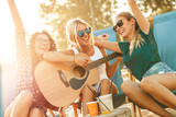 Group of young female friends sitting on beach on sunbeds,singing and playing guitar.