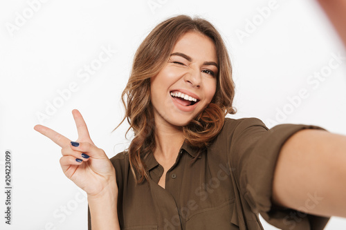 Portrait of a smiling young woman taking selfie