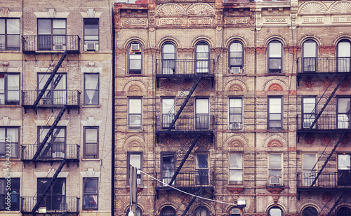 Poster Old buildings with fire escapes, one of the New York City symbols, color toned picture, USA.