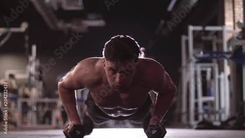 Wall mural Muscular man with dumbbell doing push ups