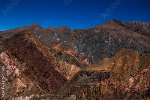 Fotobehang Diepbruine View of Iruya village and multicolored mountains in the surroundings at sunset, Salta province, Argentina, iruya - San Isidro - San Juan treeking