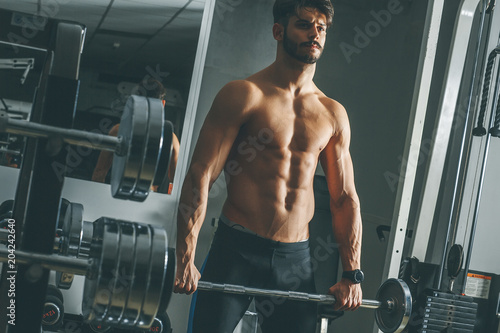 Wall mural Strong and handsome young man doing exercise with dumbbells