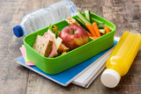 Healthy school lunch box: Sandwich, vegetables ,fruit and juice on wooden table