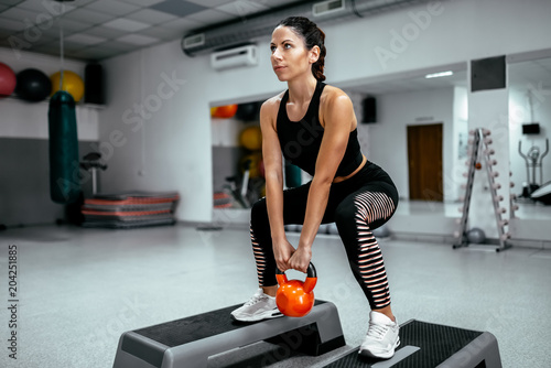 Muscular woman doing crossfit workout at gym.