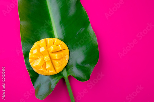 Foto Spatwand Roze Creative layout made of summer tropical fruits mango and tropical leaves on pink background. Flat lay. Copy space. Tropical food concept.