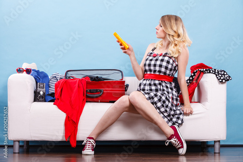 Foto Murales Young woman packing suitcase on couch