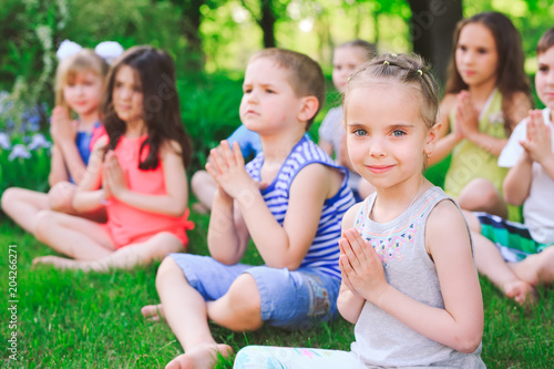 Aluminium School de yoga A large group of children engaged in yoga in the Park sitting on the grass.