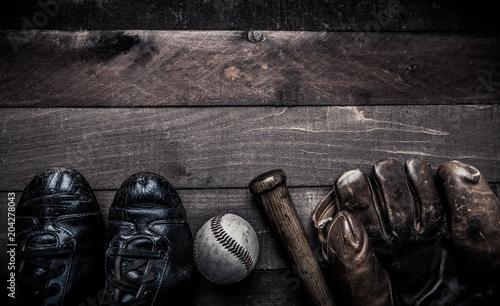 A group of vintage baseball equipment, bats, gloves, baseballs on wooden background