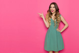 Beautiful Young Woman In Green Dress Is Pointing At Pink Copy Space And Talking